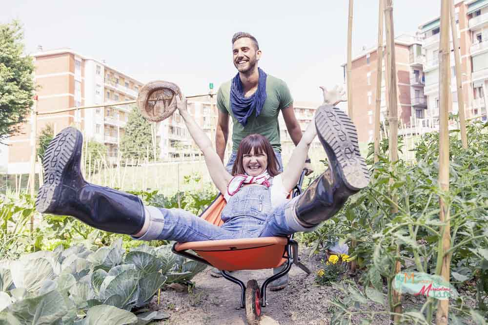 man pushes his girlfriend in wheelbarrow in the garden