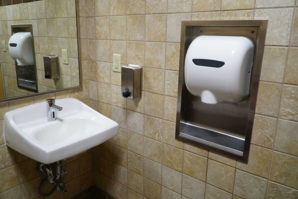 Public bathroom tiled beige with a sink, mirror, soap dispenser and automatic hand dryer.
