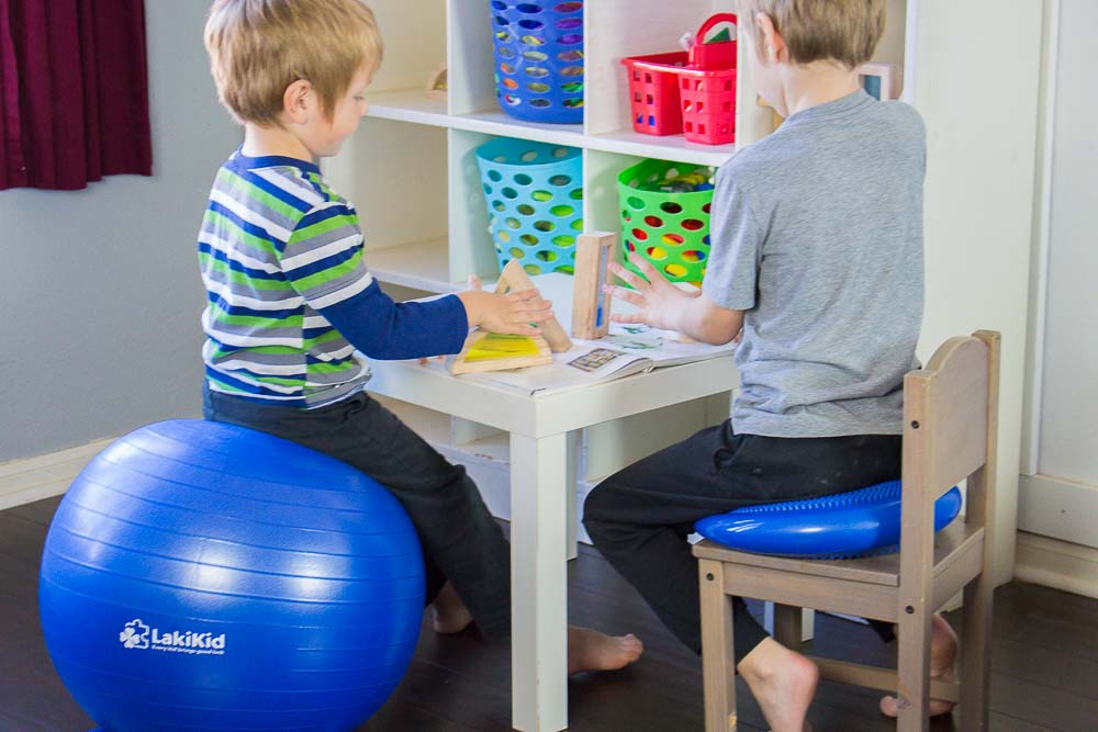 One boy sitting on an exercise ball and another boy sitting on a wiggle seat at the same table.