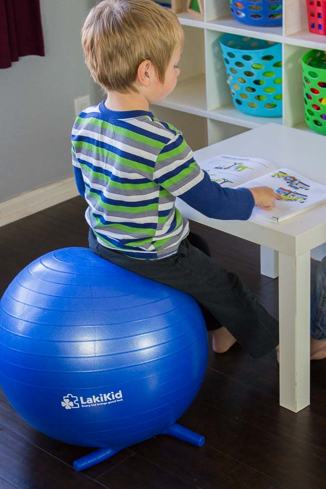 Child sitting on an exercise ball while reading a book.