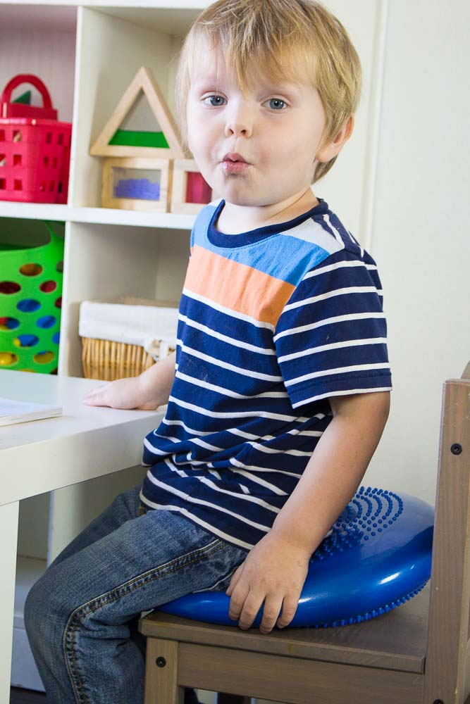 Toddler sitting on a wiggle disk.