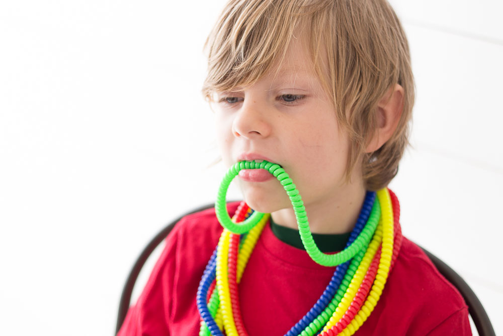 Orally sensitive child uses chewable jewelry to receive sensory input