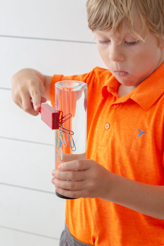 Close up shot of a boy with a neon orange shirt using a magnet on a sensory bottle filled with paper clips.
