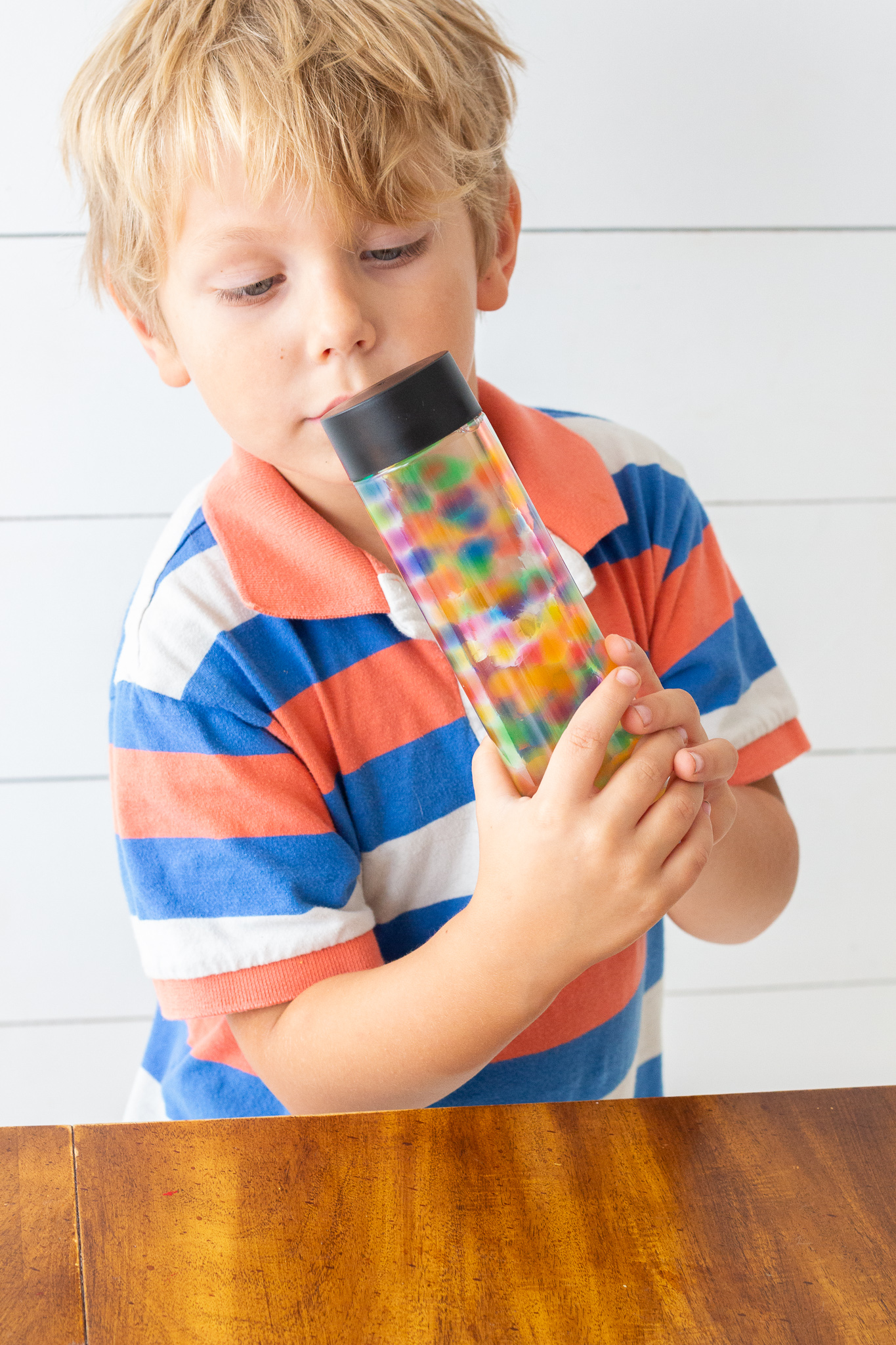 Young blonde boy shaking a sensory bottle with water beads inside.